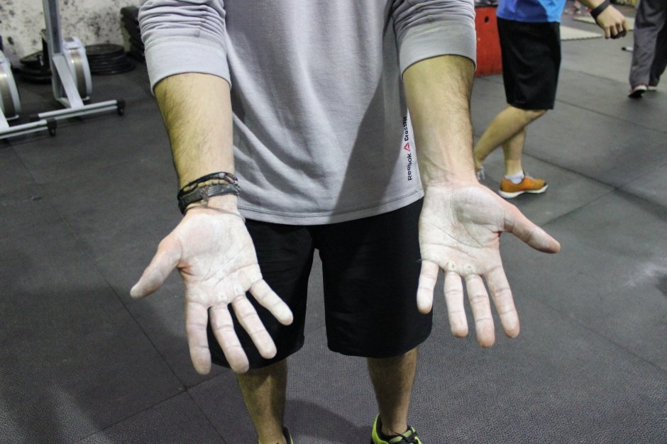 Person showing the palms of their hands with white chalk applied